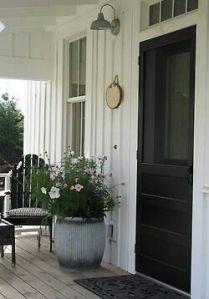 Entrée orientée au nord : porte noire, pot gris, fleurs blanche, chaise noire